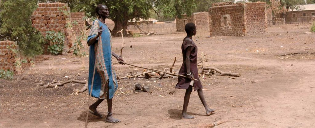 Awal 50, is blind from river blindness. Arop, a girl living on the compound leads Awal with a stick.