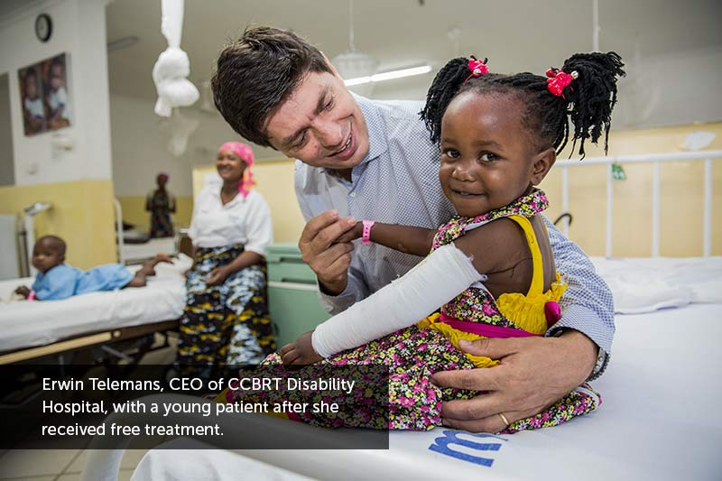Erwin Telemans, CEO of CCBRT Disability Hospital, with a young patient after she received free treatment.