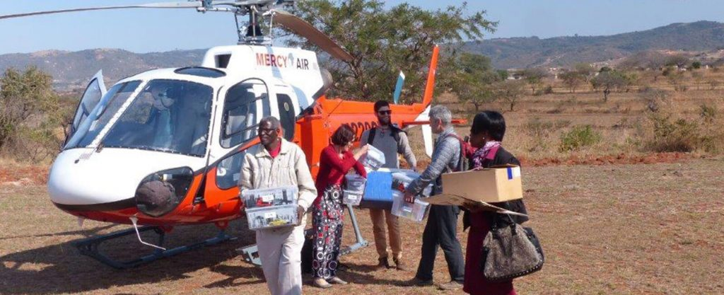 Health workers and volunteers coming out of helicopter