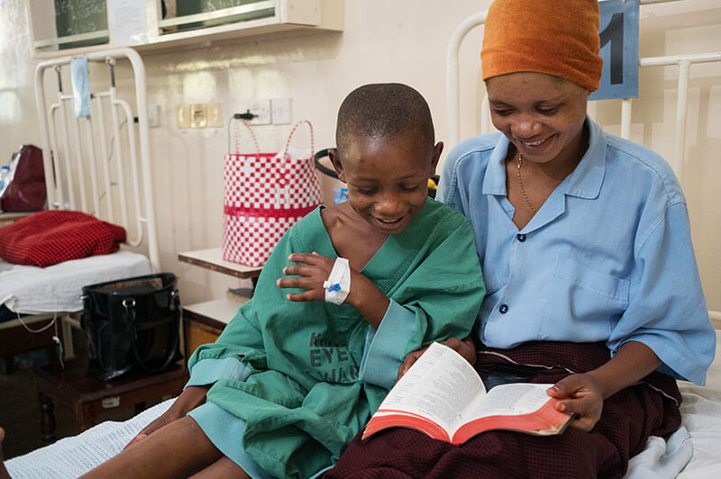 Ester and her aunt Edina read the Bible before surgery
